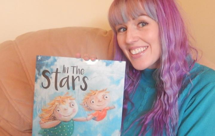 "Sam Kitson with her book ""In the Stars"""